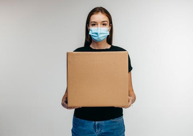 Linda jovem entregadora usando máscara nasal e carregando uma caixa de papelão em branco
