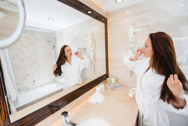 Linda jovem escovando os dentes em um banheiro branco lindo. bom dia fresco no hotel.