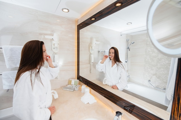 Linda jovem escovando os dentes em um lindo banheiro branco