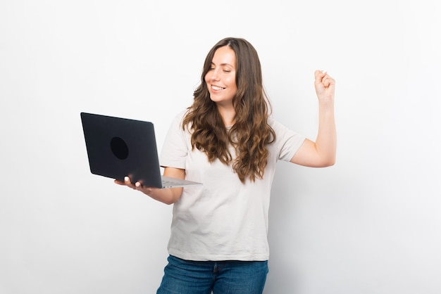 Linda jovem está fazendo o gesto vencedor, segurando um laptop.