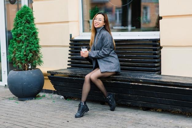 Linda jovem estudante chinesa segurando uma xícara de café na rua