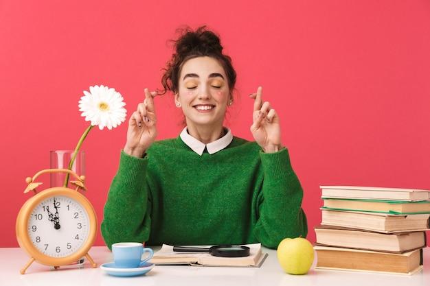 Linda jovem estudante nerd sentada à mesa isolada, estudando com livros, dedos cruzados