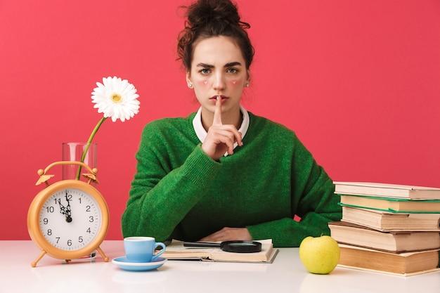 Linda jovem estudante nerd sentada à mesa isolada, estudando com livros, gesto de silêncio