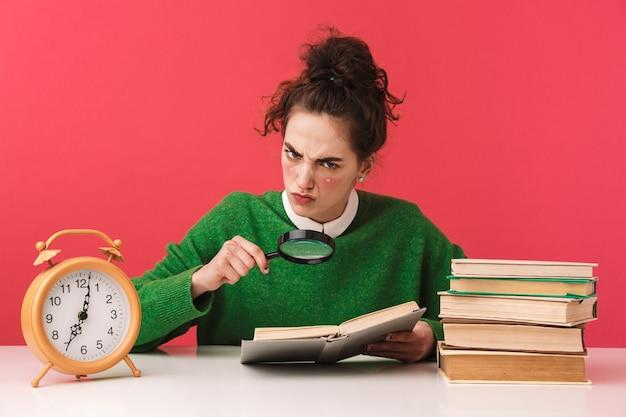 Linda jovem estudante nerd sentada à mesa isolada, estudando com livros, lupa