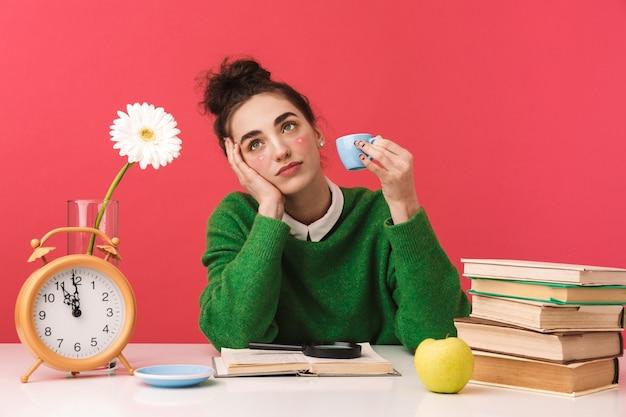 Linda jovem estudante nerd sentada à mesa isolada, estudando com livros,