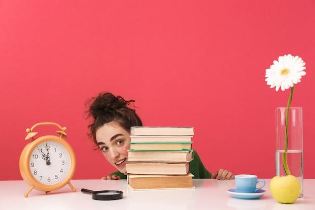 Linda jovem estudante sentada à mesa isolada, estudando com os livros, olhando para fora