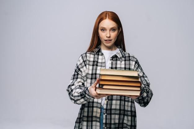Linda jovem estudante universitária segurando livros e olhando para a câmera em um fundo isolado