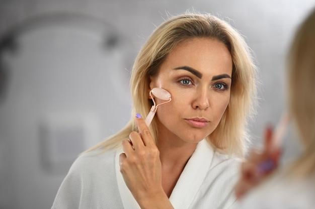 Linda jovem europeia olhando para seu reflexo no espelho e massageando o rosto com um massageador de pedra de rolo de jade, realizando massagem facial de drenagem linfática