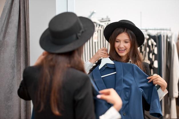 Linda jovem experimentando roupas novas na loja de moda local, olhando feliz e animado estilo de vida beleza na moda glamourosa shopaholic emoções expressivo conceito.