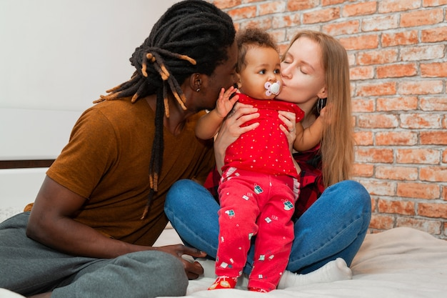 Linda jovem família com filha pequena em casa
