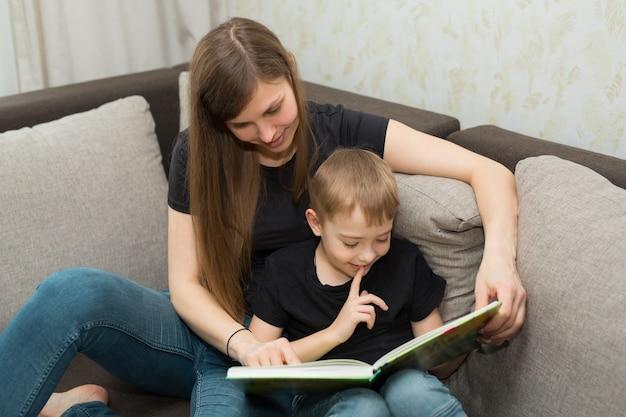 Linda jovem família mãe e filho lendo um livro em casa