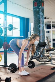Linda jovem fazendo esportes no ginásio, usando uma máscara durante a pandemia. distanciamento social em locais públicos.