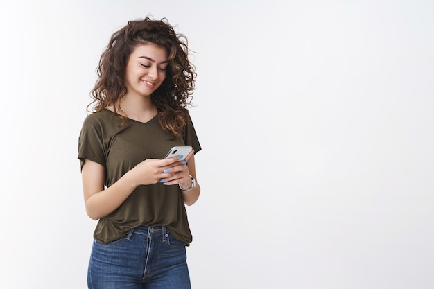 Linda jovem feliz fofa mulher bonita de cabelos encaracolados segurando um smartphone, sorrindo gentilmente, rindo, rindo, mensagens de texto com mensagens animadoras engraçadas, amigos conversando fazer atualização de perfil pessoal online