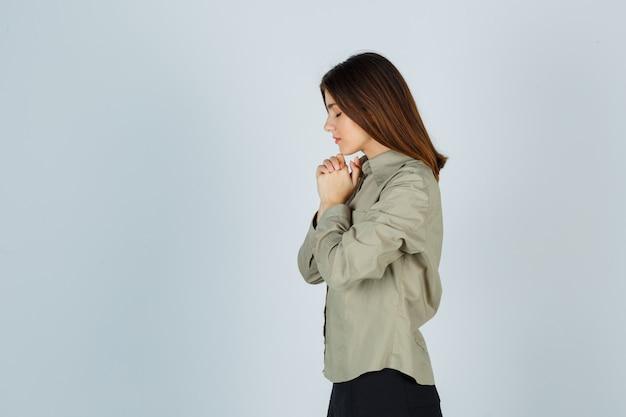 Linda jovem fêmea apertando as mãos em gesto de oração na camisa, saia e olhando esperançosa. .