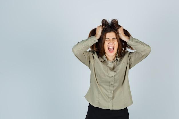 Linda jovem fêmea com camisa, saia rosnando para a câmera enquanto arranca o cabelo com as mãos e parece triste, vista frontal.