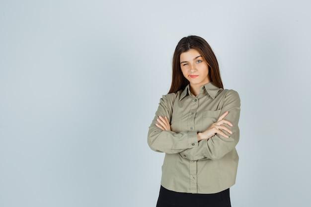 Linda jovem fêmea em camisa, saia em pé com os braços cruzados, lábios curvos, piscando e olhando pensativa, vista frontal.