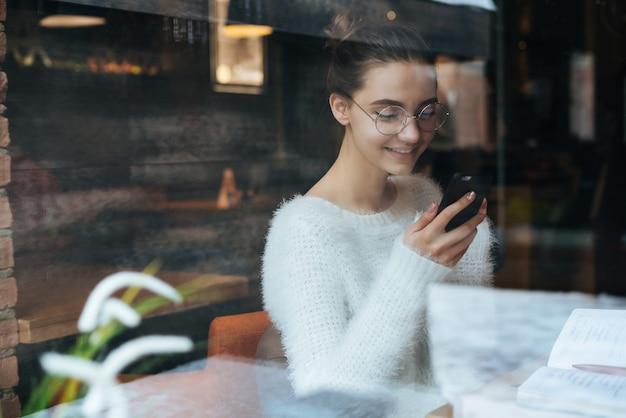 Linda jovem freelancer de jaqueta branca e óculos, olhando para o smartphone e sorrindo