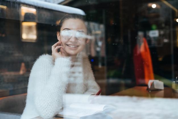 Linda jovem freelancer sentada em um café, usando óculos, falando no telefone e sorrindo