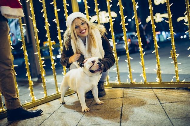 Linda jovem girll desfrutando na noite de natal ou ano novo em uma rua da cidade com seu bulldog francês.