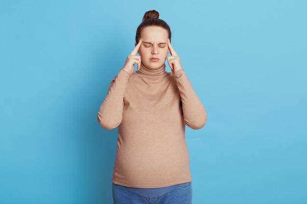 Linda jovem grávida de olhos fechados esperando bebê, mantendo os dedos nas têmporas, pensa em algo importante, posa isolada na parede azul, fica confusa e irritada.