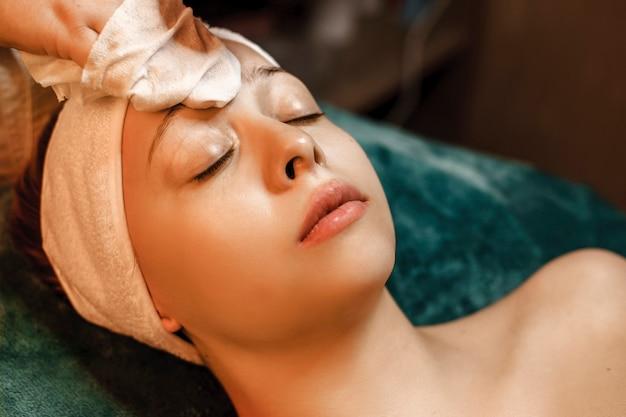 Linda jovem inclinada com os olhos fechados durante o procedimento de cuidados da pele em um salão de spa de bem-estar.