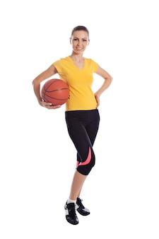 Linda jovem isolada em roupas esportivas com basquete
