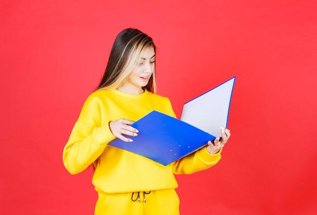 Linda jovem lendo documentos dentro de uma pasta azul na parede vermelha