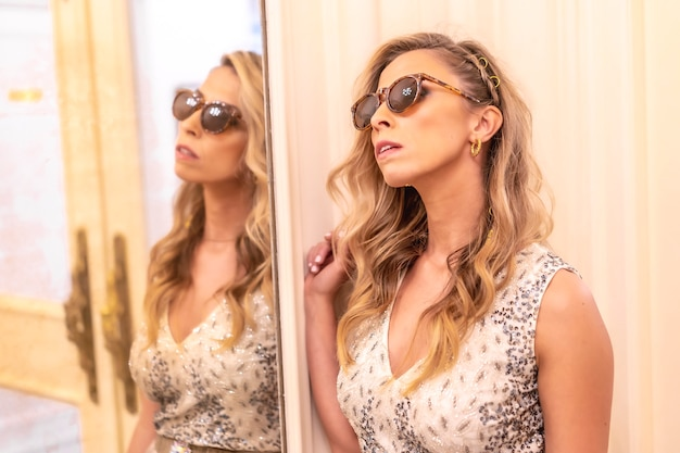 Linda jovem loira caucasiana em um vestido de baile com óculos escuros, ao lado de um espelho