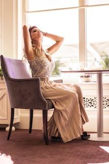 Linda jovem loira caucasiana em um vestido de baile pronta para um jantar romântico no restaurante do hotel