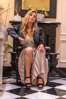 Linda jovem loira caucasiana em um vestido de baile, sentada em uma poltrona preta no hotel