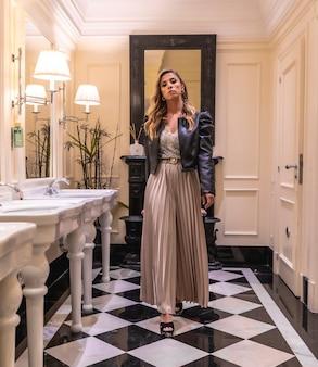 Linda jovem loira caucasiana em um vestido de noite e uma jaqueta de couro preta