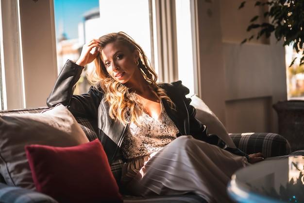 Linda jovem loira caucasiana no sofá do hotel onde está hospedada de férias