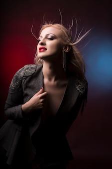 Linda jovem loira com cabelo em movimento no estúdio