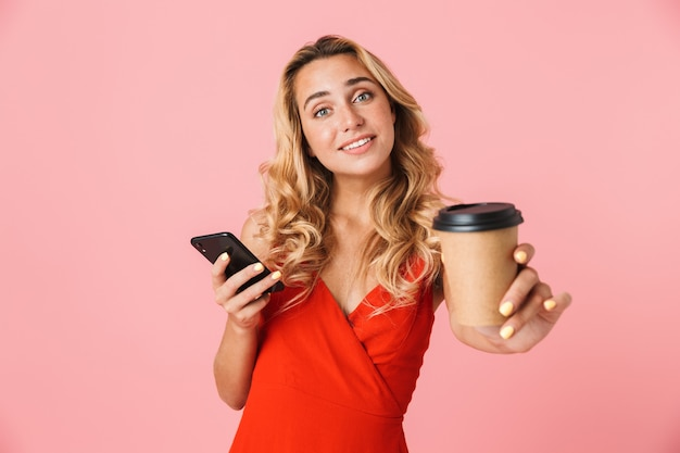 Linda jovem loira com um vestido de verão em pé, isolada na parede rosa, usando o telefone celular enquanto mostra a xícara para viagem