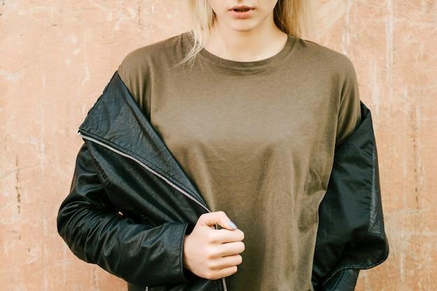 Linda jovem loira com uma camiseta verde em branco e uma jaqueta de couro