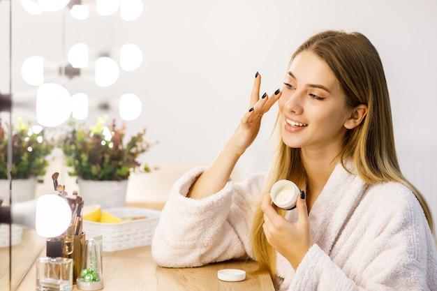 Linda jovem loira cuida da pele do rosto com hidratante em frente ao espelho