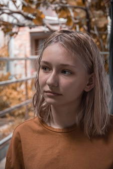 Linda jovem, loira, fica no contexto das folhas de outono e arbustos, com luz natural em tempo nublado.
