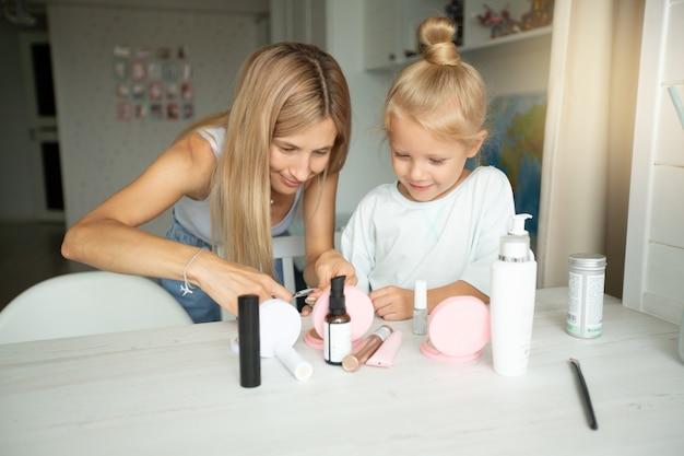 Linda jovem mãe apara as unhas de suas filhas