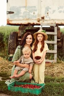 Linda jovem mãe caucasiana com seus filhos em um vestido de linho com uma cesta de morangos reúne uma nova safra e se diverte com as crianças perto do trailer