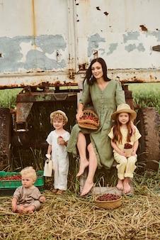Linda jovem mãe com seus filhos em um vestido de linho com uma cesta de morangos reúne uma nova safra e se diverte com as crianças perto do trailer