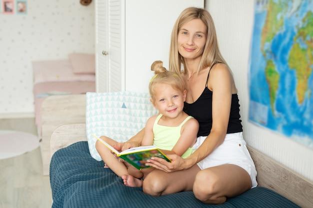 Linda jovem mãe com sua filha lendo um livro
