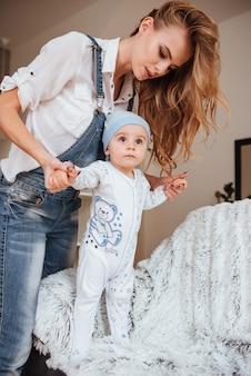 Linda jovem mãe de pé e cuidando do filho pequeno em casa