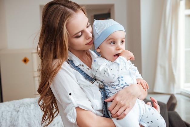 Linda jovem mãe de pé e segurando seu filho pequeno em casa