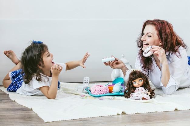 Linda jovem mãe e filha com pratos de brinquedo, doces e bonecas brincando de chá feliz