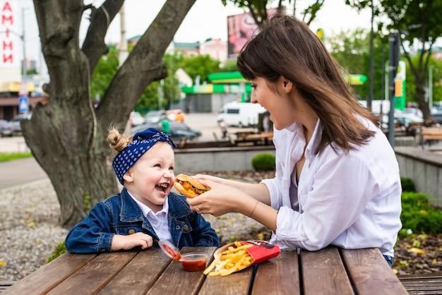 Linda jovem mãe e filha comendo um grande hambúrguer em um café