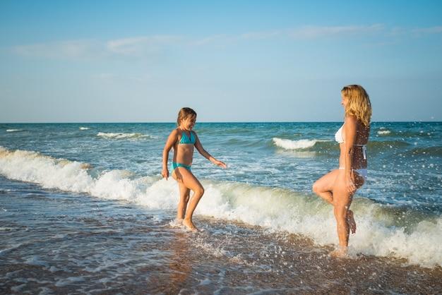 Linda jovem mãe e filha correm na beira-mar durante as férias em um dia ensolarado de verão contra um céu azul