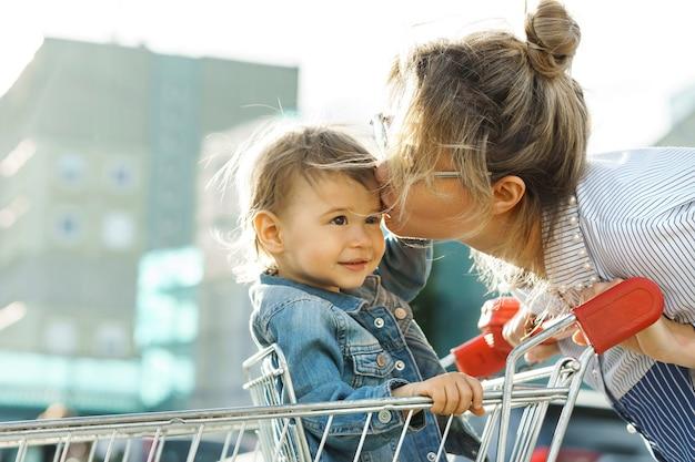 Linda jovem mãe e seu filho fofo em um carrinho de compras