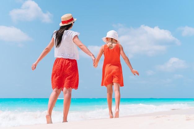 Linda jovem mãe e sua adorável filhinha se divertindo em uma praia tropical