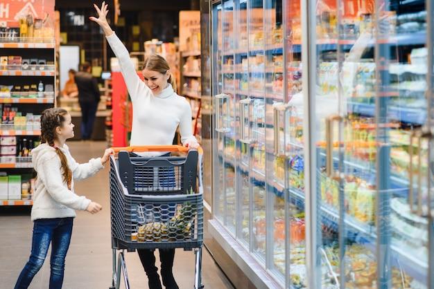 Linda jovem mãe e sua filha sorrindo e comprando comida