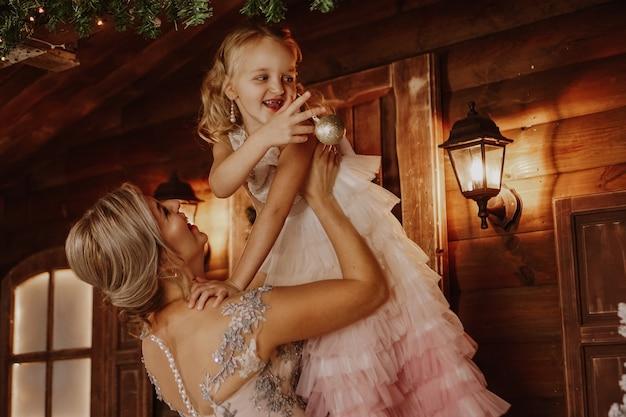 Linda jovem mãe segurando uma filha que decora uma árvore de natal